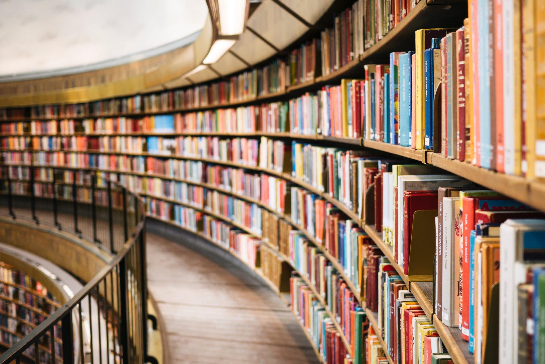 En lång bokhylla på ett bibliotek, fylld med böcker.