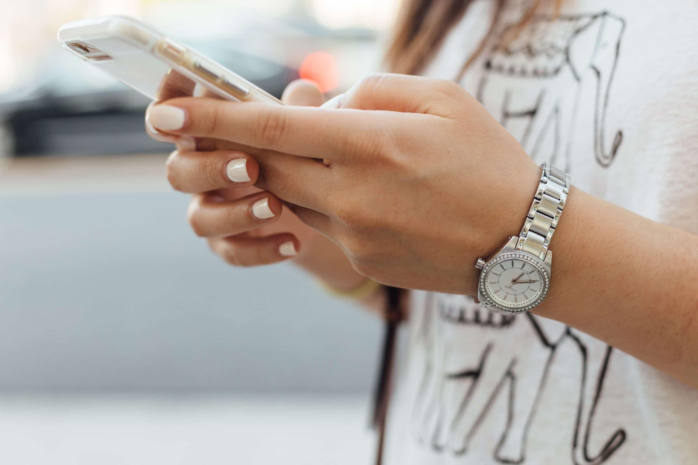 Närbild på händer som håller i en mobiltelefon.