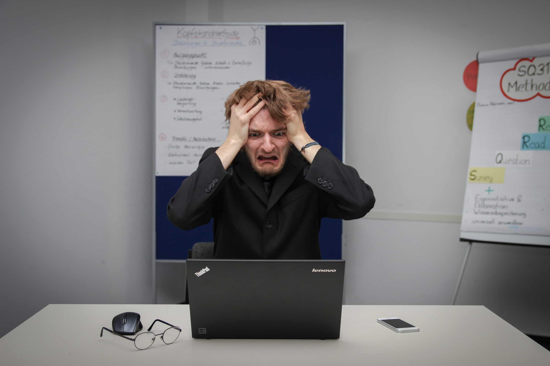 En upprörd man som tittar förskräckt på sin dator och sliter sitt hår.